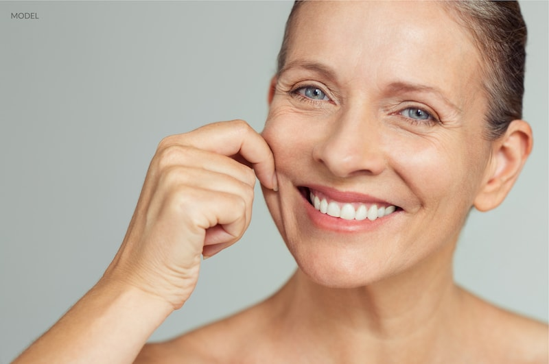 Beautiful aging woman gently pulling at her cheek skin with a smile on her face.